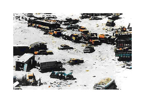 Photo of a chaos of broken-down vehicles in a parched white desert, most of them in two parallel lines as on a highway . There are all kinds of vehicles - mostly passenger cars and pickup trucks, a couple of buses, tanker trucks, cargo trucks; not a single military vehicle.